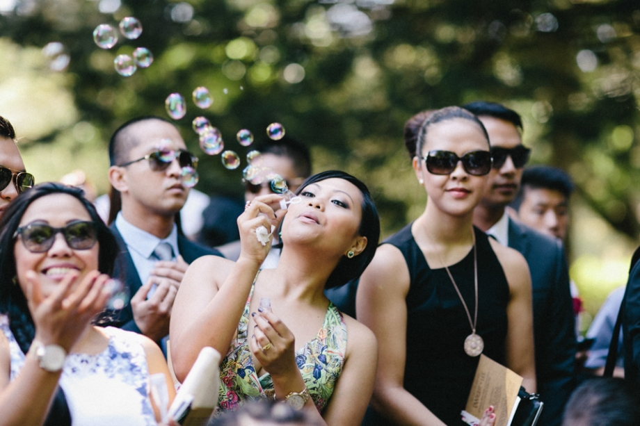 Guest blowing bubbles to celebrate wedding ceremony