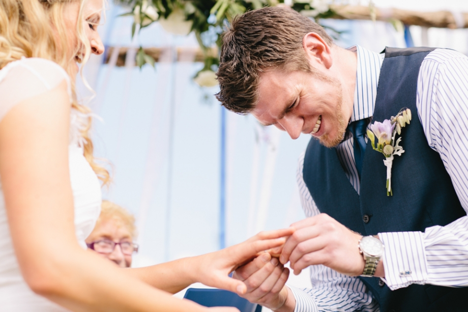 Groom putting ring on finger and laughing at ceremony