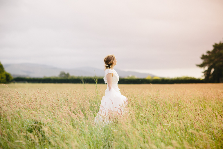 Ethereal bride in field of long grass
