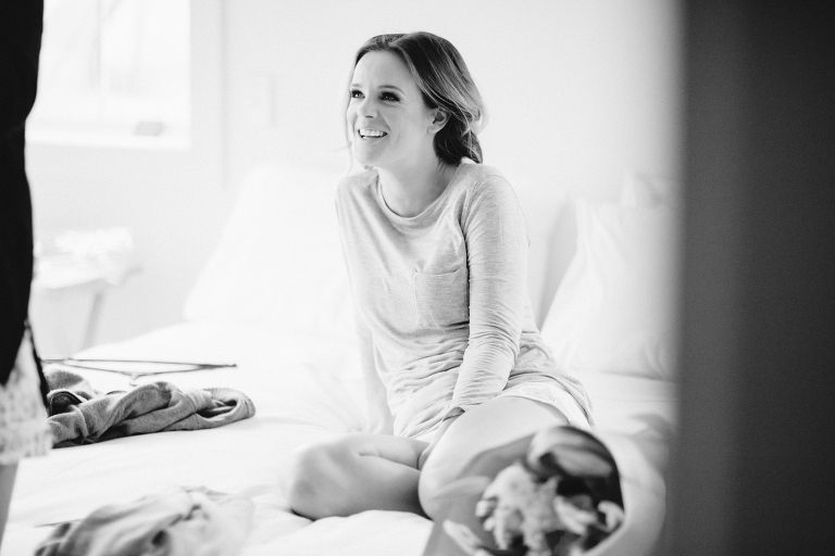 bride smiling at friend on bed Martinborough Brackenridge Estate wedding black and white