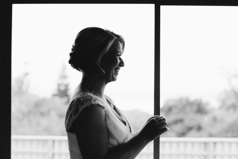 Bridesmaid smiling at bride getting dressed Riversdale Wedding natural light black and white