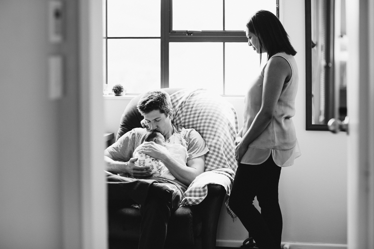 father holding baby girl on his chest with mom looking on Newborn Photography Wellington black and white